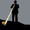 silhouette monochrome of alpine horn player with horn