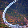 fighter jets performing tight bends in mountainous regions