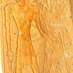 Pharaoh wearing the ram's horn crown holds Ankh's in his hands while receiving the gift of life from Osiris, from the early new kingdom mortuary temple of Queen Hatshepsut at Thebes in Egypt