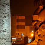 Giant statues of Ramses  II enthroned and the great obelisk in front of the ancient egyptian temple of Luxor in the town centre. Egypt
