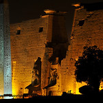 Illuminations of the ancient egyptian temple of luxor with giant statues of Ramses II enthroned and the great obelisk