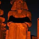 Enthroned colossal statue of Ramses II at the Luxor Temple in Egypt at night