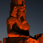 colossal seated sculpture of the pharaoh Ramses II at night at the ancient Luxor Temple in Egypt