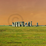 Red sky over the entire circle of standing stones at Stonehenge in England, with Salisbury plain in the background at the summer solstice