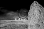The heal stone with the rest of Stonehenge in the background and behind that Salisbury Plain at the summer solstice