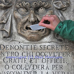 a woman pushes a discreet note into the lion's mouth, in the doge's palace, Venice. For centuries the Venetian state relied on the public to denounce crimes using this lion's mouth.